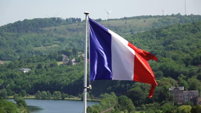 ms shot of forest behind french flag / sierck les bains, lorraine, france - lorraine stock-videos und b-roll-filmmaterial