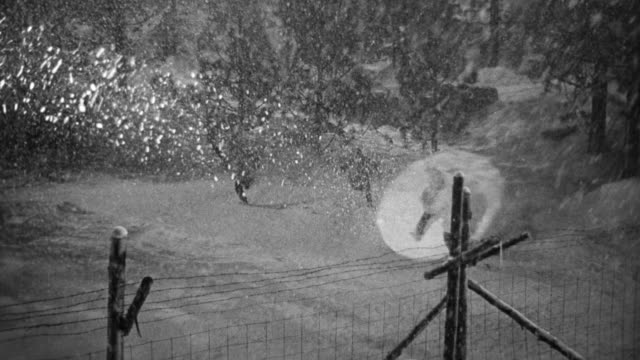 WS HA Shot of forest covering in snow with trees and portion of POW camp with men escaping from camp are chased and captured