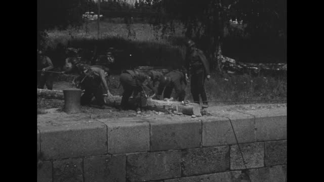 shot of forest / soldiers carrying log / shot of canal / soldiers pushing log onto wall of canal / soldier lowering himself by rope onto bank of... - lowering stock videos & royalty-free footage