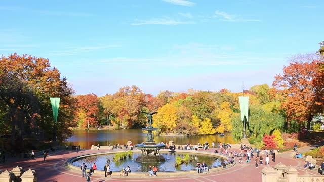 WS PAN HA Shot of fountain and people and autumn color trees at Bethesda Terrace at sunset / New York, United states