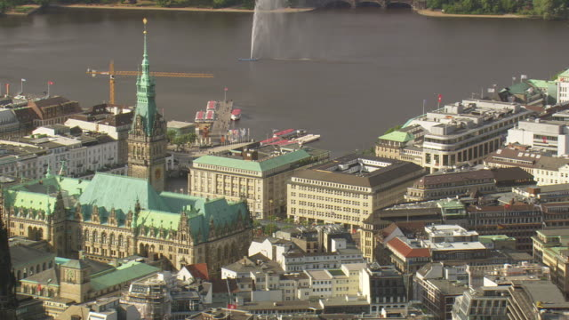 MS AERIAL ZO Shot of fountain in Alster lake with buildings / Germany