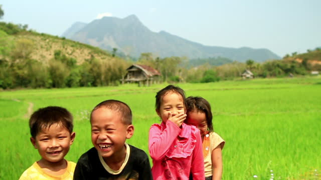 MS SLO MO Shot of four children laughing , rice paddies / Hmong, Luang Prabang, Laos