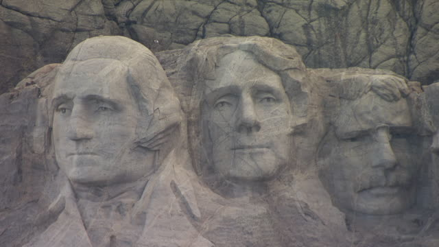 cu aerial ts zo shot of four faces of george washington and thomas jefferson and theodore roosevelt and abraham lincoln mount rushmore in pennington county / south dakota, united states - ジョージ・ワシントン点の映像素材/bロール