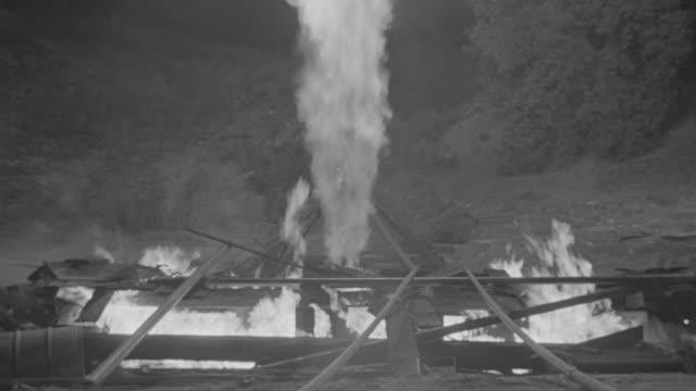 ms shot of four men enter to putting fire, flames shooting up - 緊急用具点の映像素材/bロール