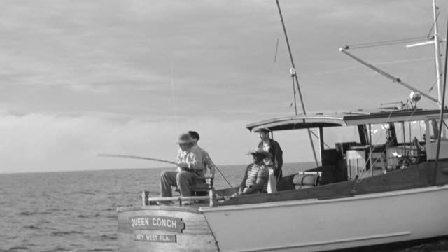 WS Shot of Four men standing on small boat fishing, one hitting bullet