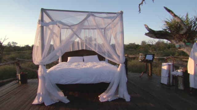 vídeos de stock, filmes e b-roll de ms pan shot of four poster bed on outdoor wooden platform, valley of rainbow, dullstroom / mpumalanga, south africa - áfrica meridional
