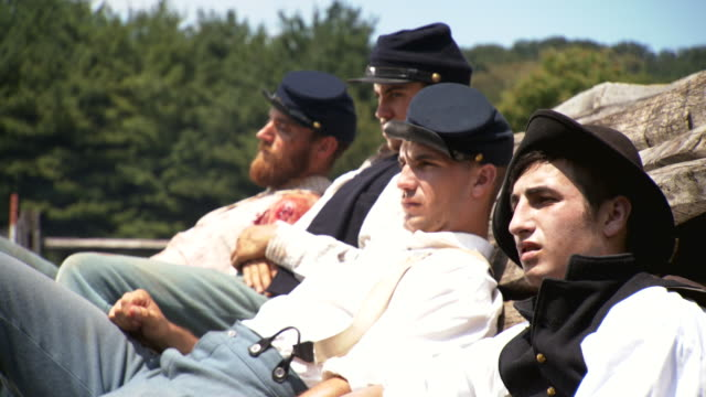 vídeos de stock, filmes e b-roll de ms pan shot of four wounded union soldiers rest against fence / clear spring, maryland, united states - exército da união