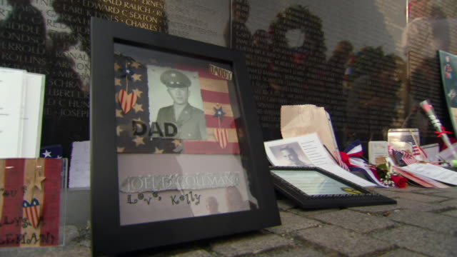 MS Shot of Frame picture of soldier among other mementos left at Vietnam Veterans Memorial Wall / Washington, District of Columbia, United States