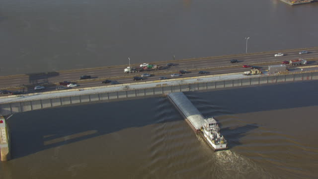 ms aerial ts shot of freight boat on mississippi river going under bridge / st louis, missouri, united states - westward expansion stock videos & royalty-free footage