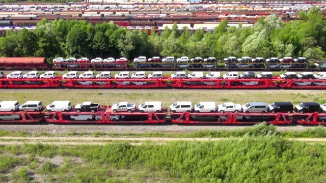 vídeos de stock e filmes b-roll de ms pov aerial shot of freight trains loaded with cars and containers at terminal / munich, bavaria, germany - carregar