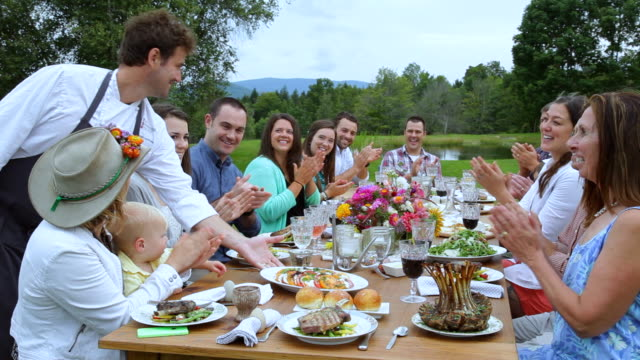 ws shot of friends clapping together on table and one man serving food dish, outside / manchester, vermont, united states - manchester vermont stock videos & royalty-free footage