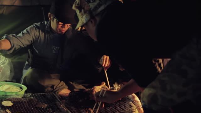 ms pan shot of friends cooking food at camp site in night / okutama, tokyo, japan - 男の友情点の映像素材/bロール