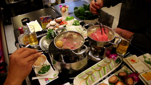 ms shot of friends in restaurant to eat hot pot / xian, china - chinese culture stock videos & royalty-free footage