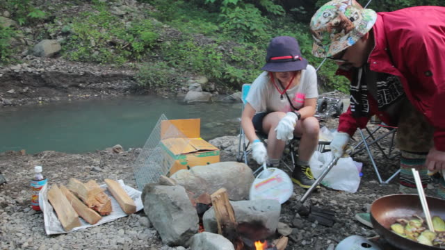 ms pan shot of friends make fire at camping / okutama, tokyo, japan - hand fan stock videos and b-roll footage
