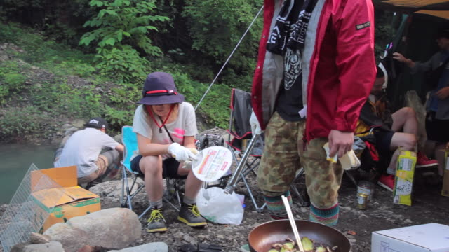 ms pan shot of friends make fire for cooking food at camping / okutama, tokyo, japan - okutama area stock videos & royalty-free footage