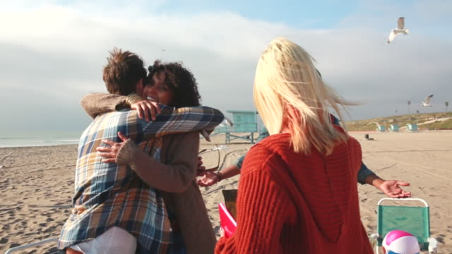 MS SLO MO TU Shot of friends meeting at beach, hugging / Venice, California, United States