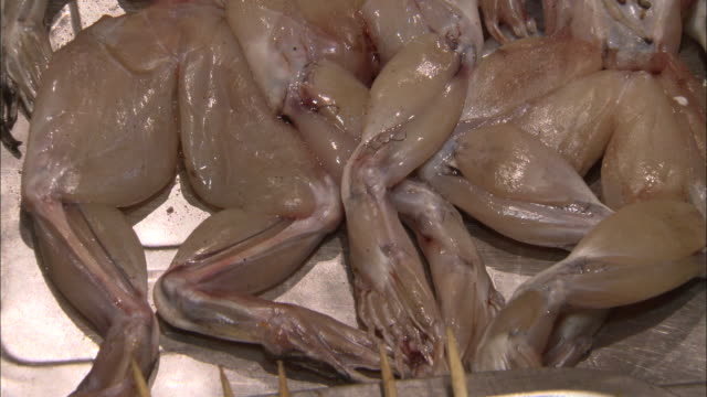 vidéos et rushes de shot of frog legs at a night market in kaifeng, china - culture chinoise