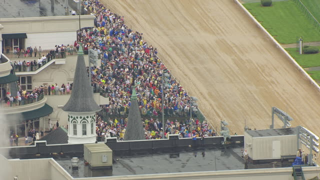 ms aerial shot of front of churchill downs rotating around spires and stands to crowds / louisville, kentucky, united states - pferderennbahn stock-videos und b-roll-filmmaterial