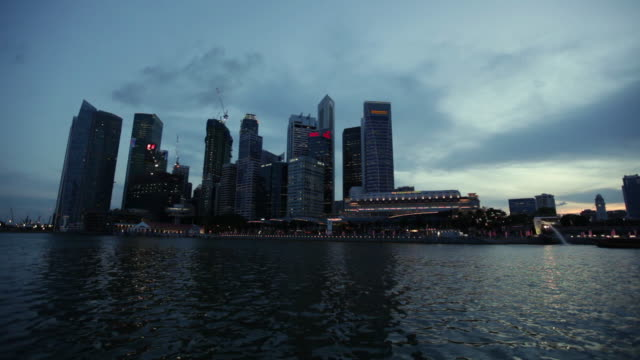 MS POV Shot of futuristic city buildings form boat / Singapore