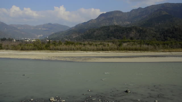 ws pan shot of ganges river with mountains in background / rishikesh, uttarakhand, india - acqua santa video stock e b–roll
