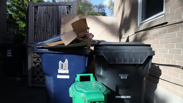 MS Shot of Garbage, compost, and recycling cans with stack of cardboard boxes at side of house / Toronto, Ontario, Canada