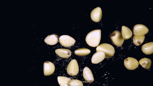 cu slo mo shot of garlic, allium savitum, falling on water against black background / calvados, normandy, france - garlic stock videos & royalty-free footage