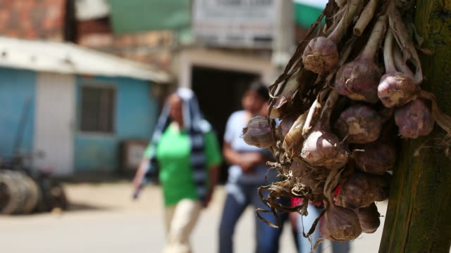 MS Shot of garlic heads for sale and pedestrians walking by / Bogota, Colombia