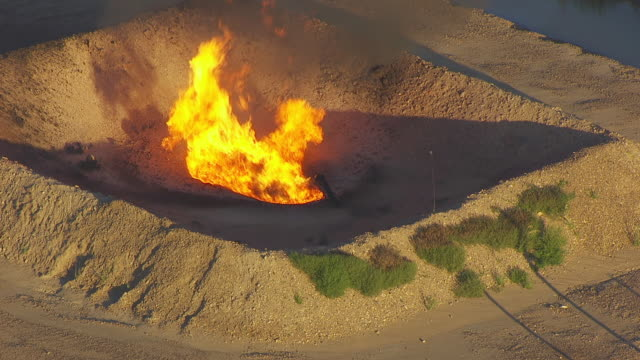 CU AERIAL TS ZO Shot of Gas flare burns in pit at oil well at Williston Basin / North Dakota, United States