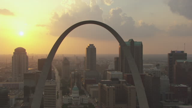 MS AERIAL TS ZO Shot of Gateway Arch at sunset with downtown buildings in back side / St Louis, Missouri, United States