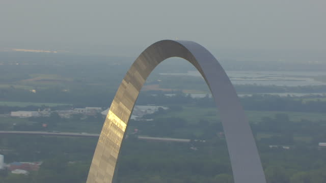 MS AERIAL Shot of Gateway Arch at sunset with low buildings in back side / St Louis, Missouri, United States
