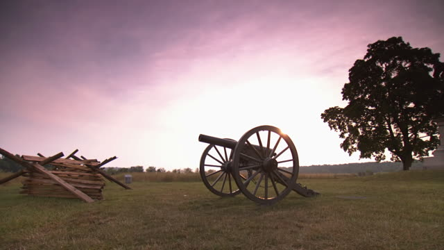 ms pan shot of general hancock monument next to cannon and wooden fence at gettysburg national military park during sunrise / gettysburg, virginia, united states - cannon stock videos & royalty-free footage
