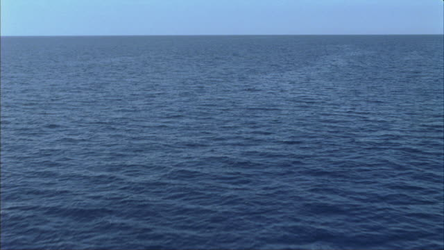 POV shot of gentle ripples rolling in an expansive ocean as seen from a moving boat.