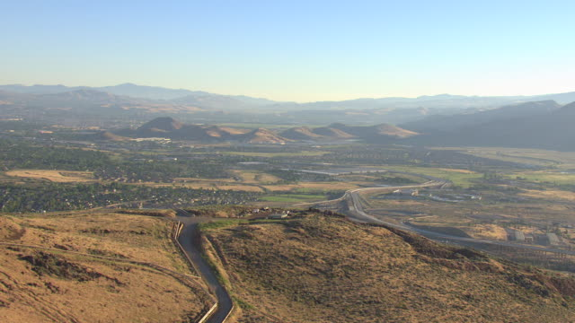 ms aerial tu shot of geothermal plant releasing steam into air and town in valley and surrounding mountains in morning sunshine / steamboat hills, nevada, united states - hügelkette stock-videos und b-roll-filmmaterial