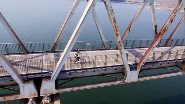 MS AERIAL TS ZO Shot of girl cycling on bridge of Namhan river / Yangpyeong, Gyeonggi-do, South Korea