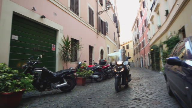 ms pan shot of girl driving scooter in alley of trastevere / rome, lazio, italy - motor scooter stock videos & royalty-free footage