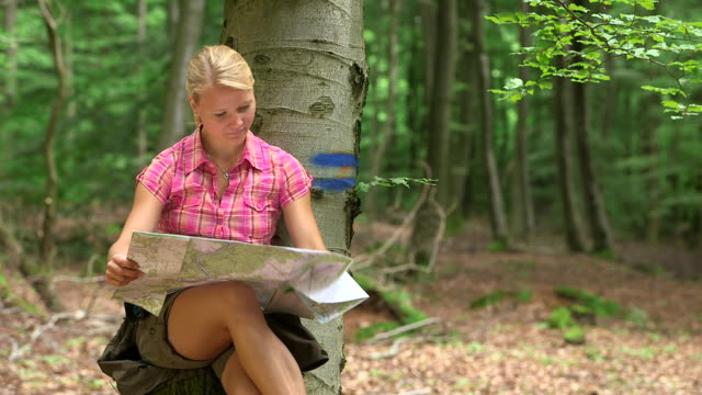 ms shot of girl having rest in wood land, looking at map / kastel staadt, rhineland palatinate, germany  - 僅年輕女人 個影片檔及 b 捲影像