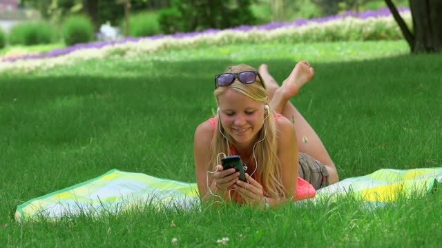 ms shot of girl laying in park on blanket and listening to music on smartphone / losheim am see, saarland, germany - one teenage girl only stock videos & royalty-free footage