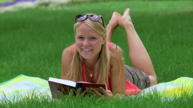 MS Shot of girl laying in park on blanket reading book and smiling / Losheim am See, Saarland, Germany