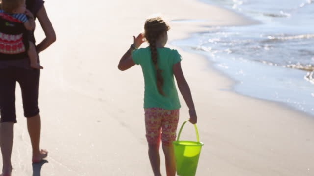 cu tu shot of girl lifting bucket in her hand, family walking on beach / st simon's island, georgia, united states - bucket stock videos and b-roll footage