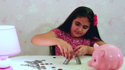 vídeos de stock e filmes b-roll de ms ts shot of girl making stack of coins / gurgaon, haryana, india - making money