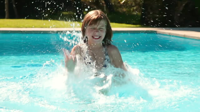 MS Shot of girl playing and smiling in swimming pool / Pollenca Mallorca, Spain