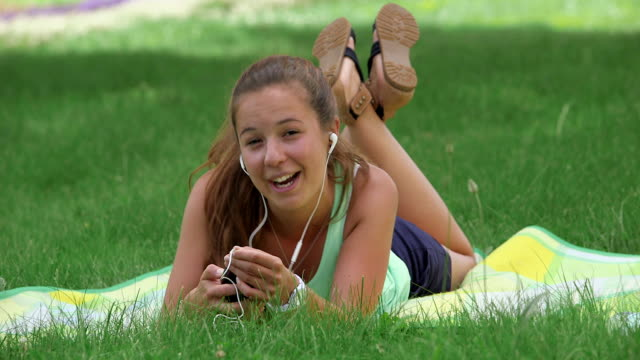 ms shot of girl sleeping in park on blanket listening to music on smartphone and singing song / losheim am see, saarland, germany - reclining stock videos and b-roll footage