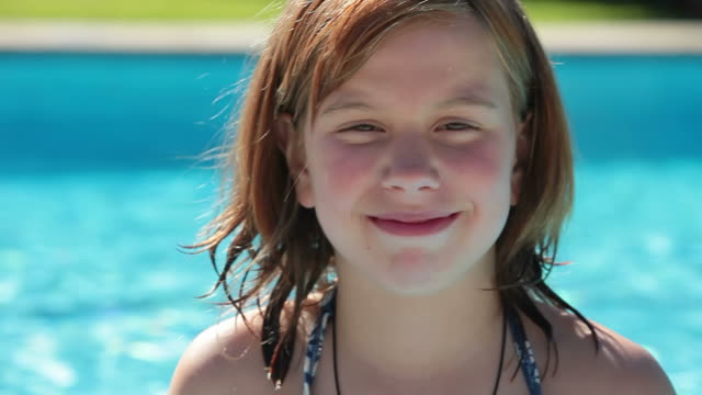 ECU Shot of girl smiling in swimming pool / Pollenca Mallorca, Spain