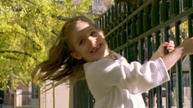 stockvideo's en b-roll-footage met cu shot of girl swinging on fence in park / new york, united states - haarband