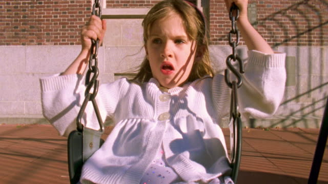 stockvideo's en b-roll-footage met ms shot of girl swinging on swing in park / new york, united states - haarband