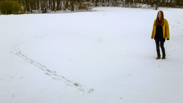 vídeos de stock e filmes b-roll de ms t/l shot of girl walking outline of heart in pristine snow / ambach, bavaria, germany - só meninas adolescentes