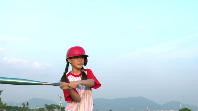 MS SLO MO Shot of Girl wearing baseball uniform with helmet swinging baseball bat / Seoul, South Korea