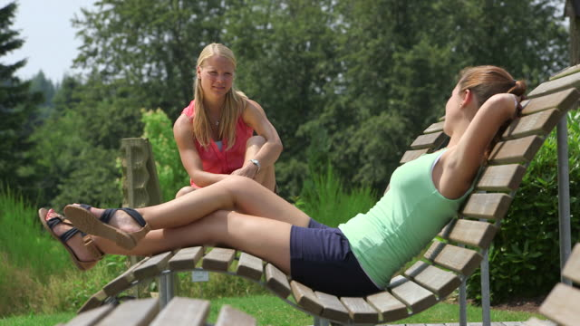 MS Shot of girls having chat at break on sun lounger on bench / Losheim am See, Saarland, Germany