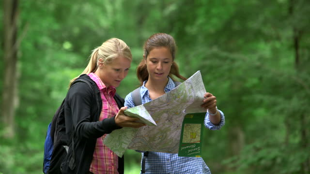 ms shot of girls hiking with map in wood land / kastel staadt, rhineland palatinate, germany  - haar nach hinten stock-videos und b-roll-filmmaterial