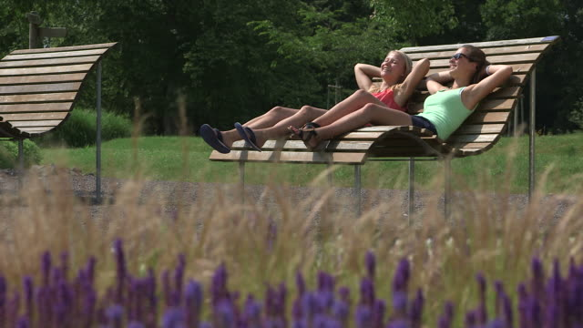 ms shot of girls in park sitting on bench and chilling in sun / losheim am see, saarland, germany - only teenage girls stock videos and b-roll footage